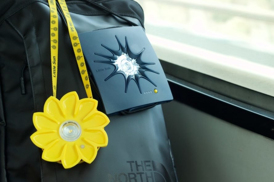 The Little Sun Original solar lamp and Little Sun Charge solar charger on a backpack