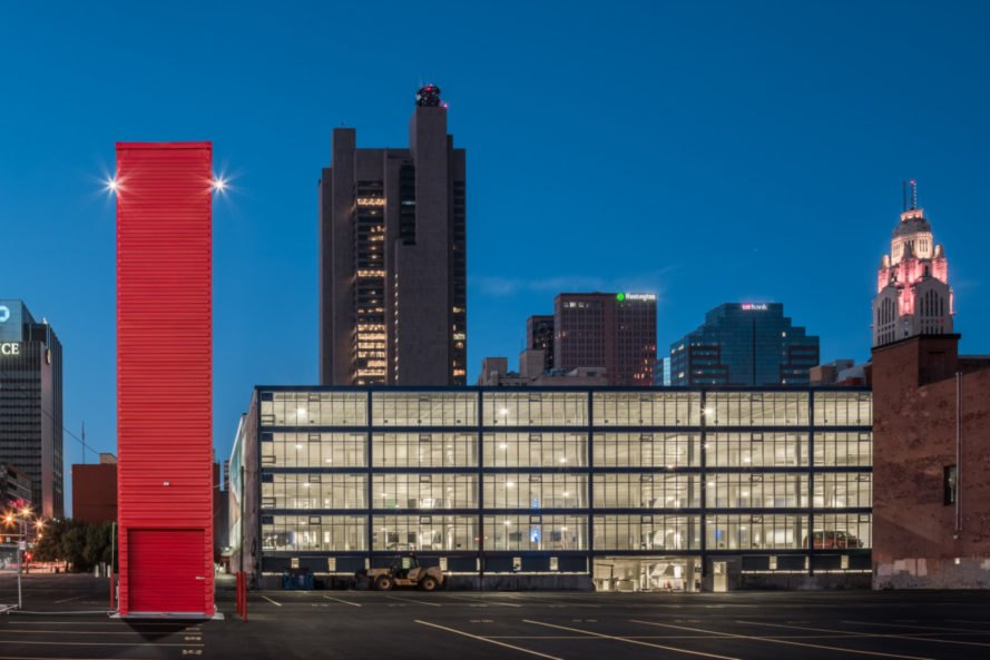tall red shipping container tower in front of a building