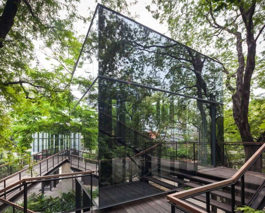 reflective building surrounded by trees