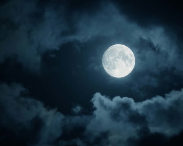 A full moon among nighttime clouds