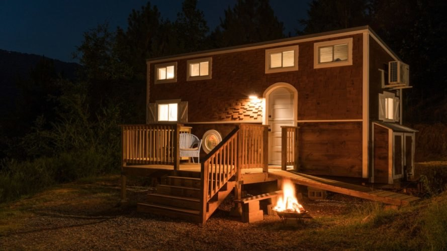 nighttime photo of tiny home with front porch