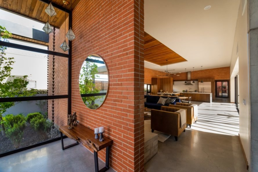 a brick separation wall with large round mirror