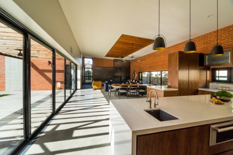 a living roo and kitchen with an all glass wall