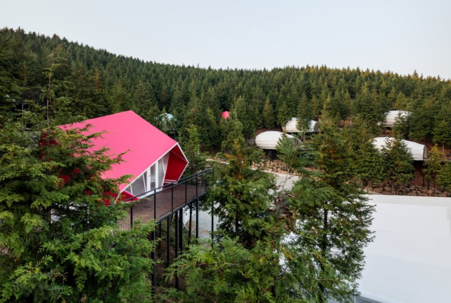 a pink building surrounded by a forest