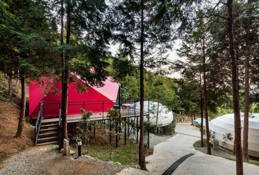a walking path leading to a pink camping pod