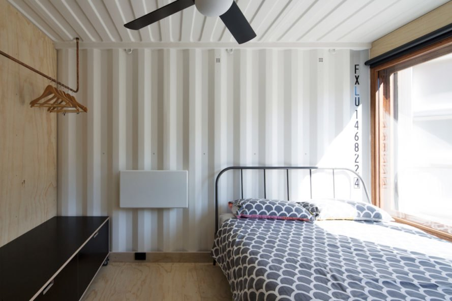shipping container walls with bed and lamp