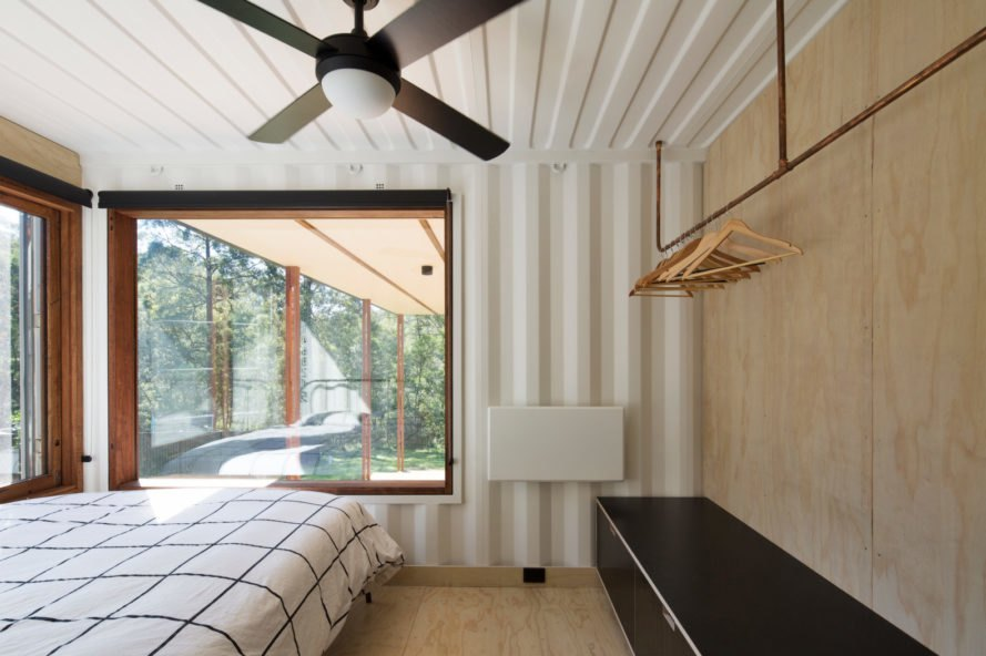 a bedroom with a bed, storage and ceiling fan