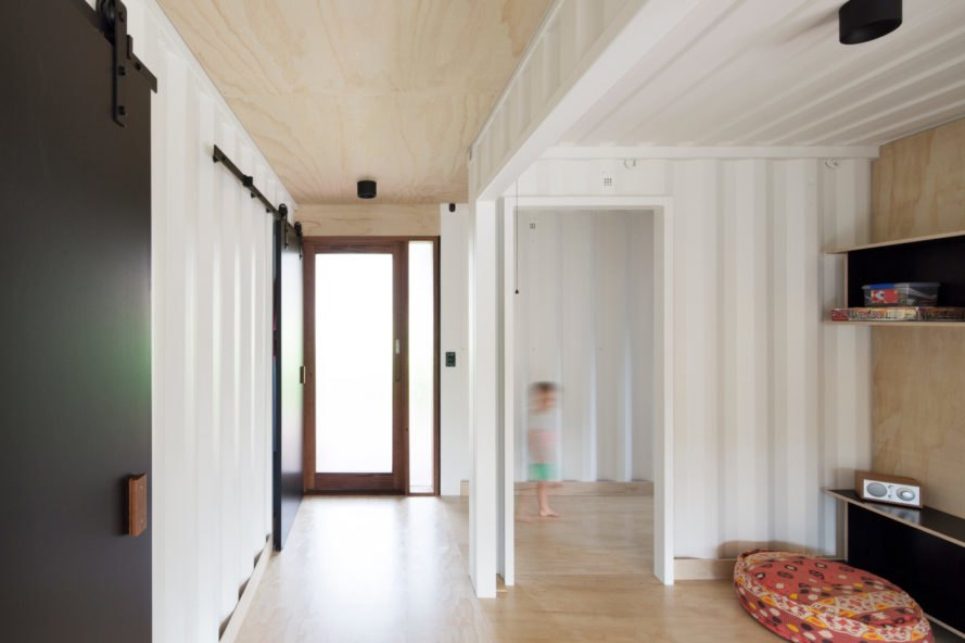 a hallway of white walls and glass door