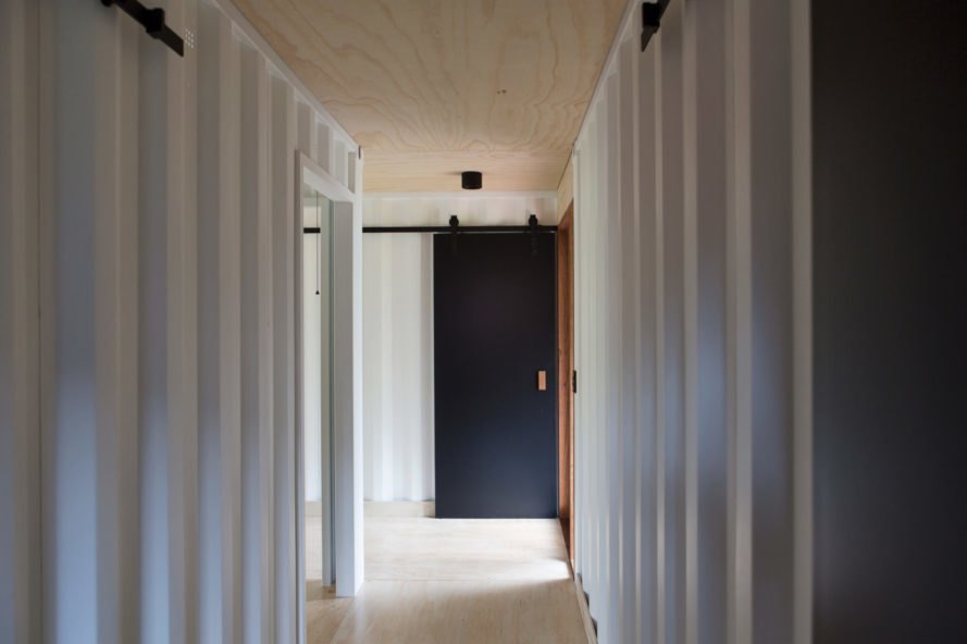 a hallway with a sliding door in the background