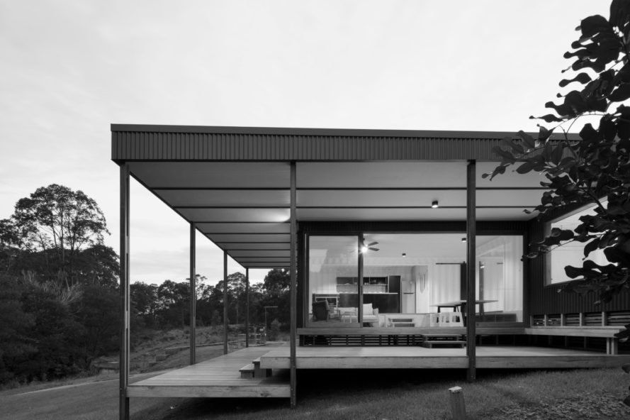 a black and white image of a home with large windows and wrap around deck