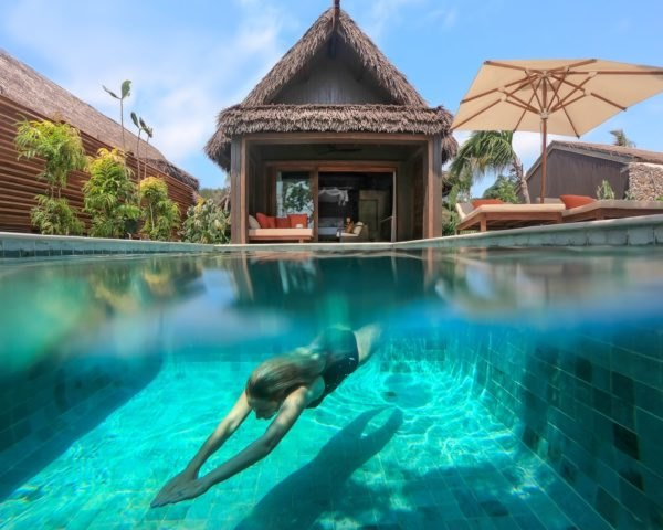 Person diving in pool in front of resort villa