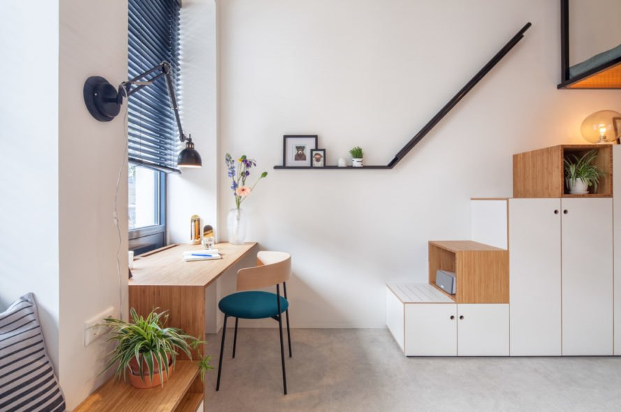 desk and chair facing out a window and stairs