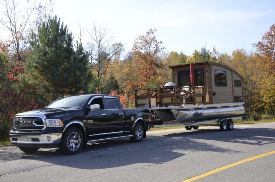 a pickup truck towing a tiny house boat