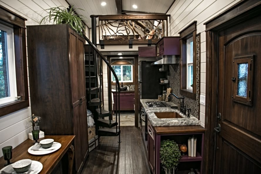 interior space of tiny home wiht white walls and dark wood flooring