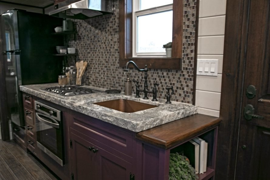 kitchen with marble countertop and mosaic backsplash