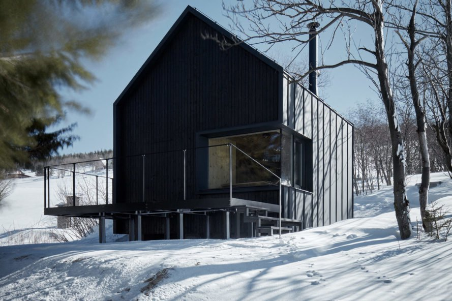 Black cabin with gabled roof and large deck