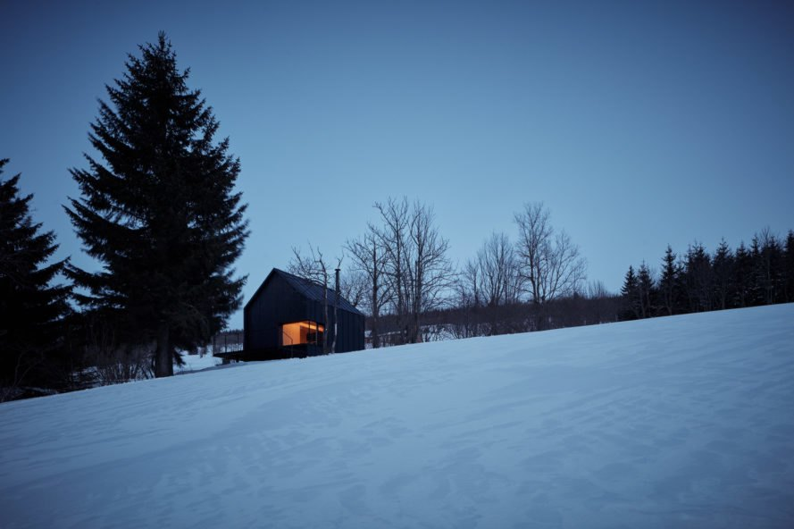 Black cabin on snowy hill at dusk