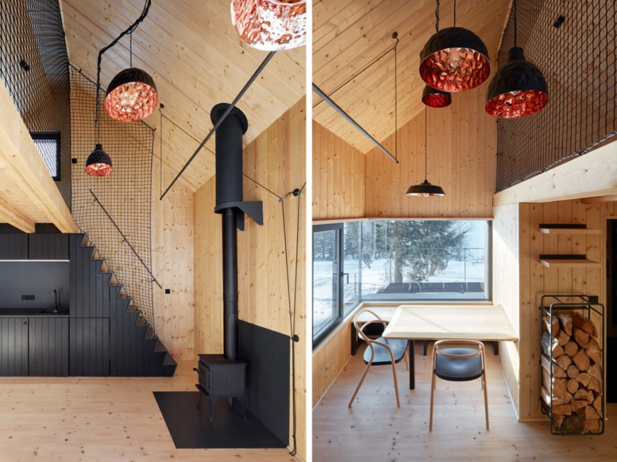 On the left, black timber kitchen and a dark wood burning stove. On the right, pendant lights hang above a small dining table