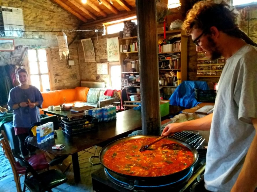 a man cooking a large pot of paella