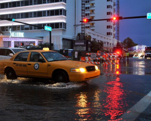 Cars driving through flooded streets of Miami Beach