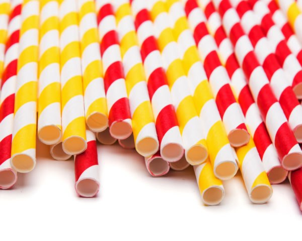 Red and yellow paper straws on white background