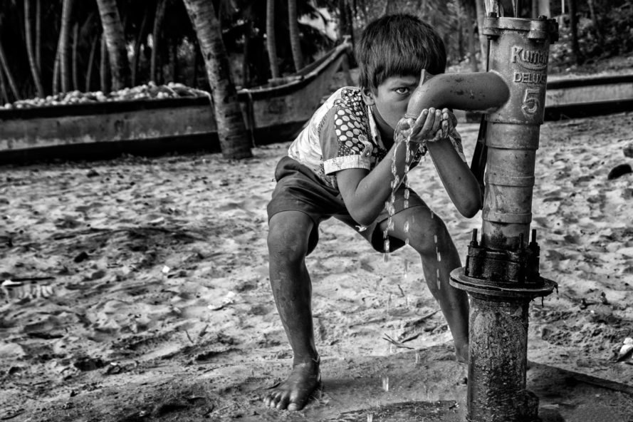 Black and white photo of child drinking water from outdoor spout