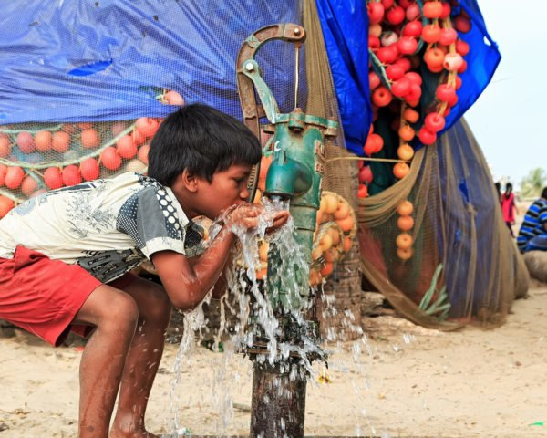 Child drinks water from an outdoor water spout