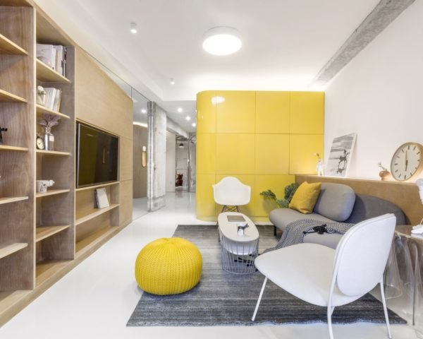 living room with timber entertainment center, gray couch, large yellow cube in background