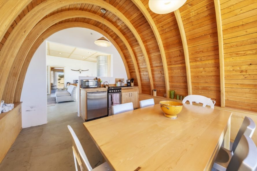kitchen and dining space with wood table, wood cabinets, and a rounded wood ceiling