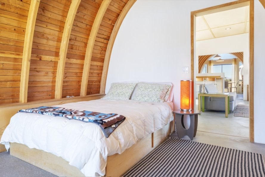 bed with white bedding and a small night stand with an orange lamp under a curved wood ceiling