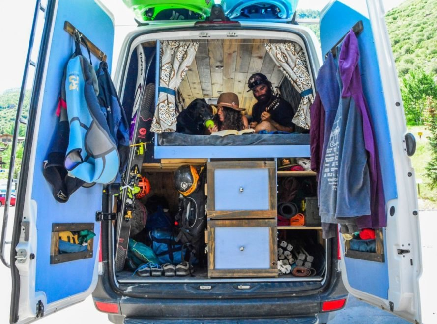 storage area in back of white van with two people above