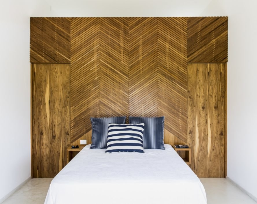 White bed with navy and white pillows in front of a wood wall with herringbone-pattern