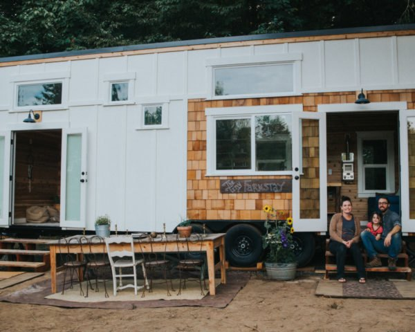 couple sitting on steps of small home exterior with white panels and cedar siding
