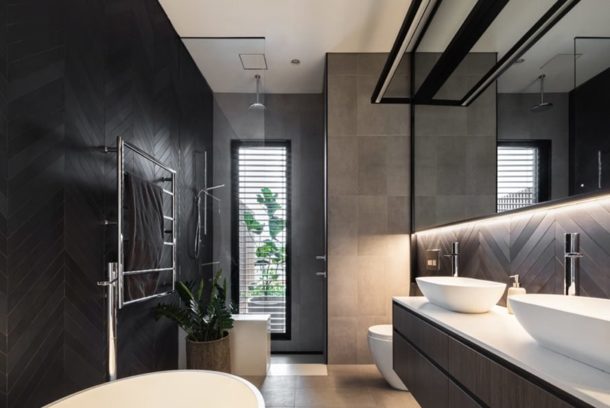 bathroom with gray and black tiling and modern sinks and toilet