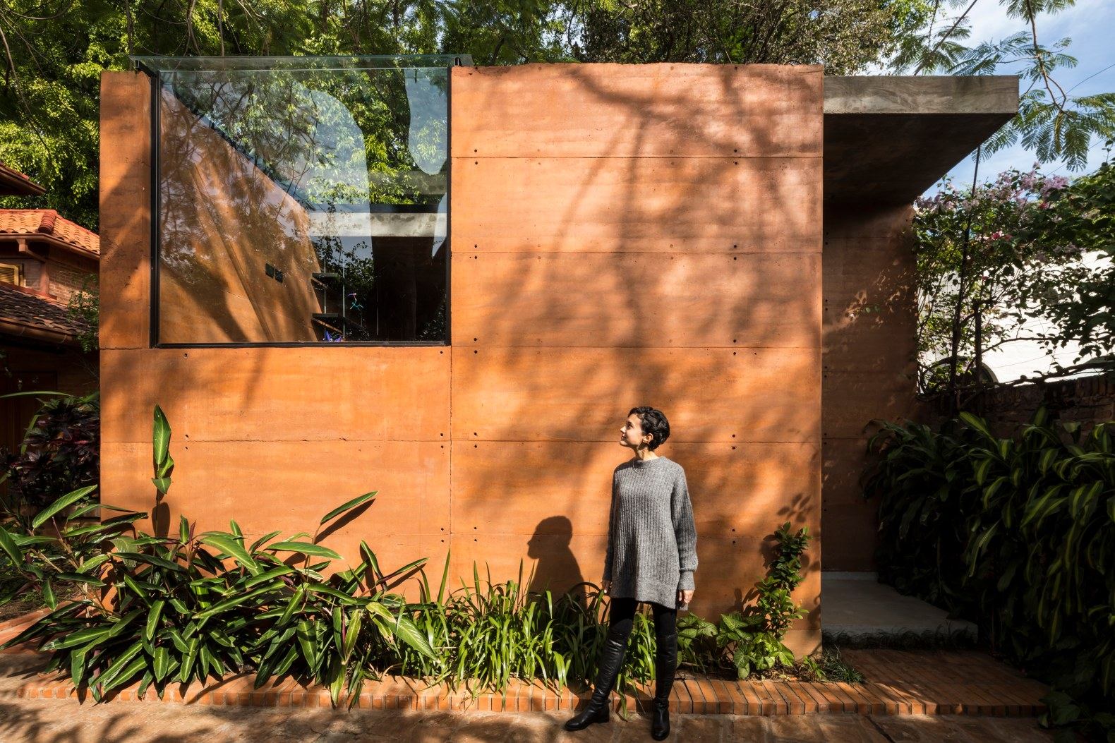 Architects build their own rammed-earth office around existing trees