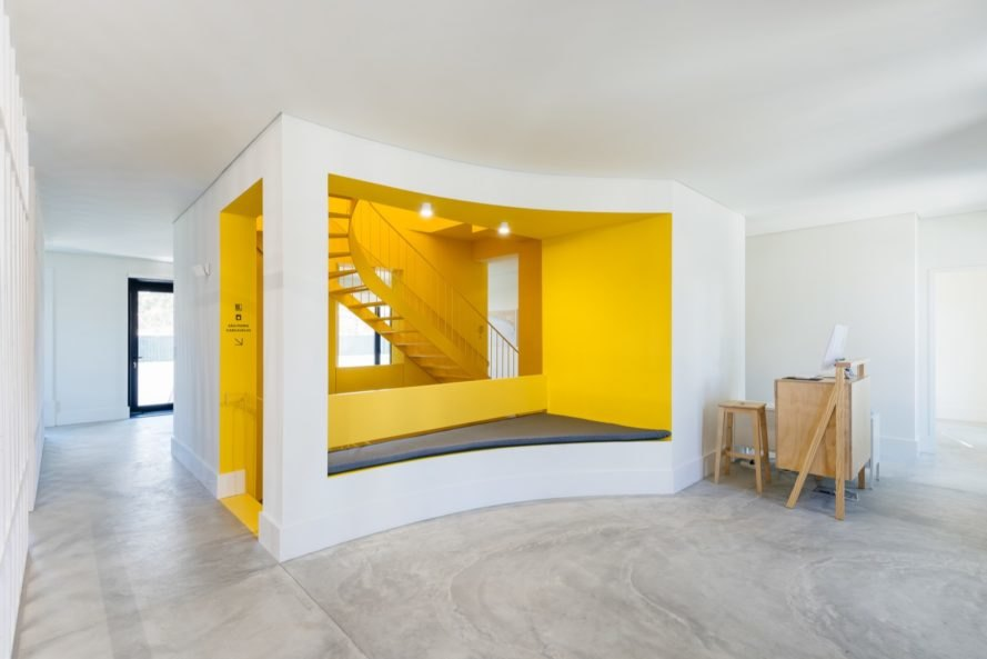 White room leading to the bright yellow staircase area