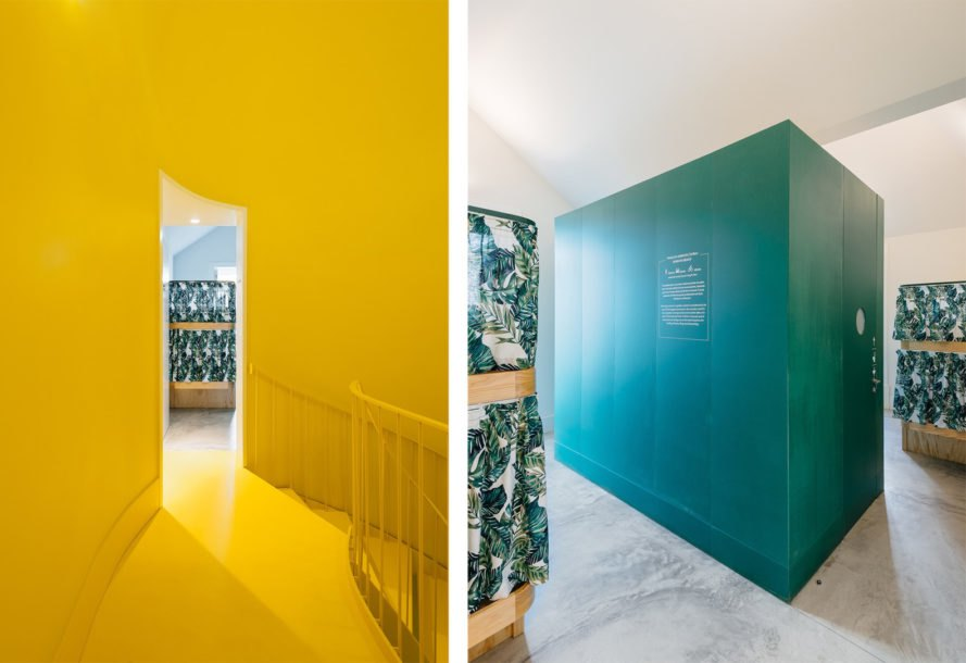On the left, bright yellow staircase. On the right, green cube in the middle of bedroom. This green cube is a bathroom unit.