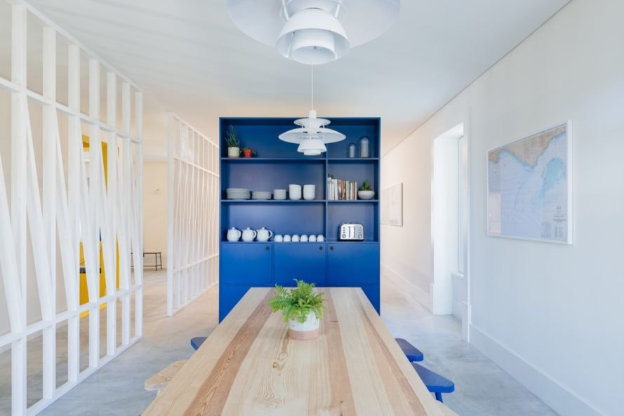 dining room with long light timber table and a tall blue shelving unit
