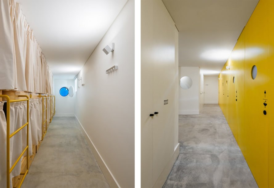 On the left, yellow bunk-beds in a row with white privacy curtains. On the right, line of bathrooms with yellow doors on a yellow wall
