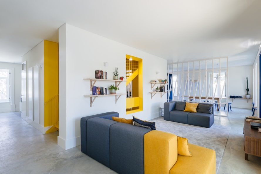 Lounge area with gray and yellow couches and books on wall shelves