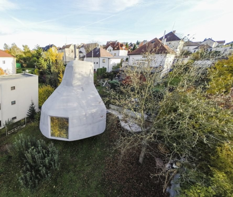 Aerial view of mushroom-shaped home surrounded by traditional homes