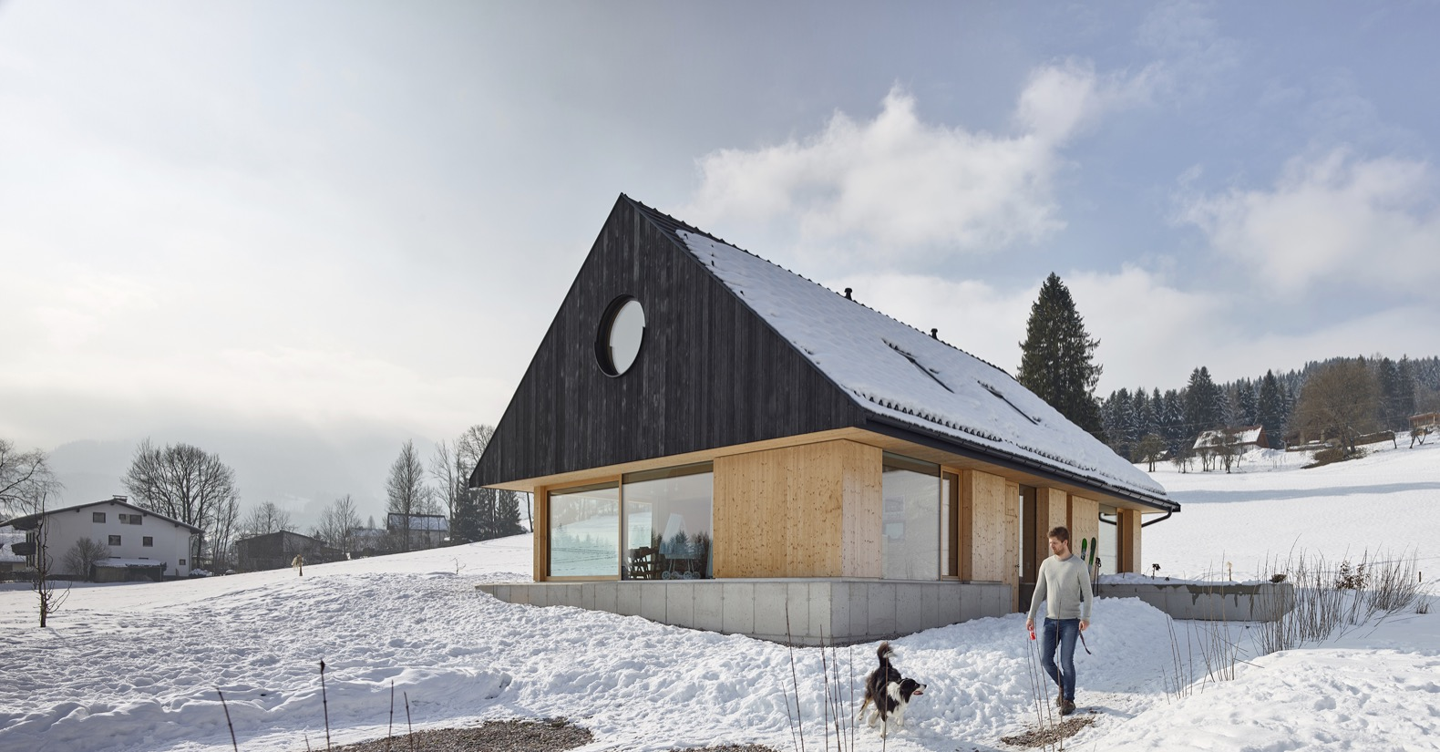 A massive gabled roof protects this minimalist timber home from the snow