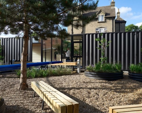 Landscaped garden in front of a black shipping container