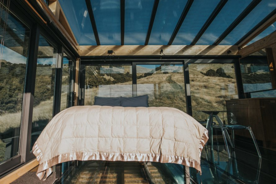 a bed in an all-glass cabin