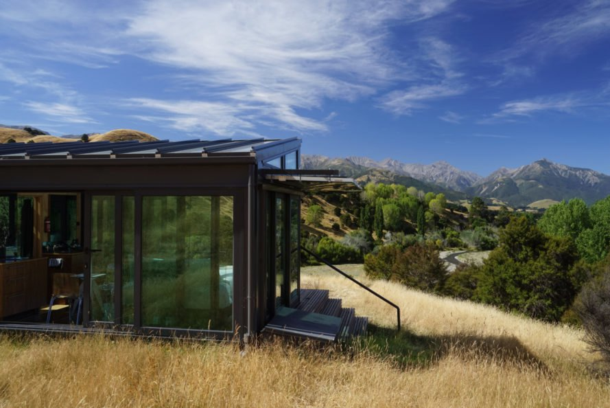 a glass cabin with stairs leading out to natural landscape