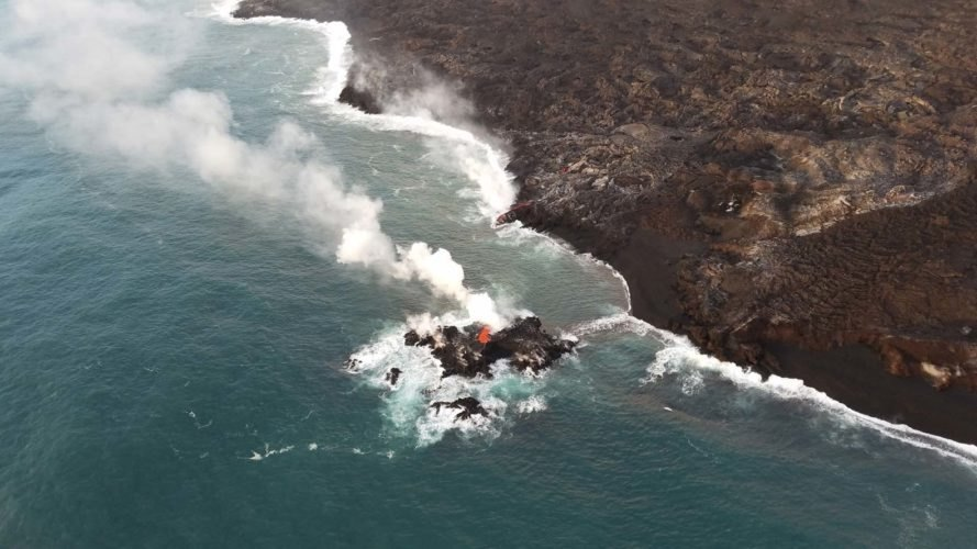 zoomed out view of new volcanic island in ocean with smoke rising in air