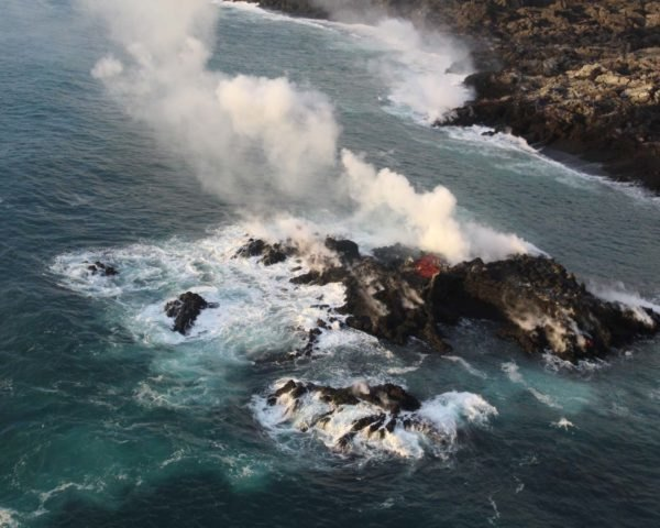 new volcanic island in ocean with smoke rising in air