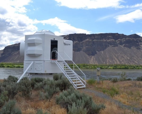 spaceship-like tiny home near river with mountains in background