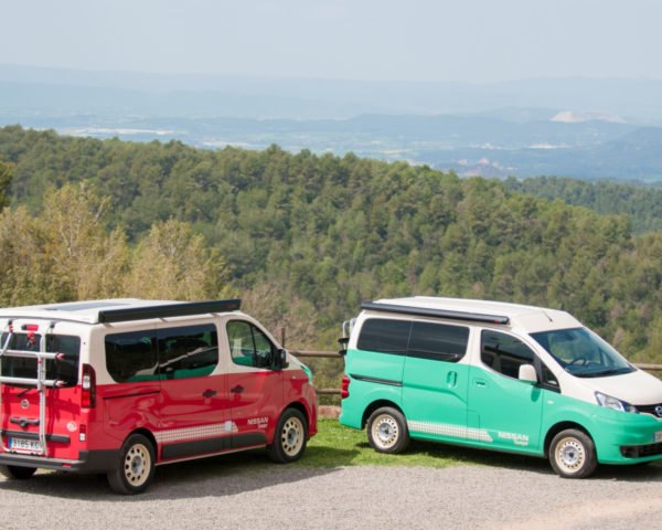 a red camper parked next to a light green camper