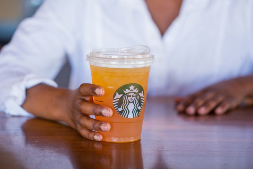 Person holding a starbucks drink with strawless lid